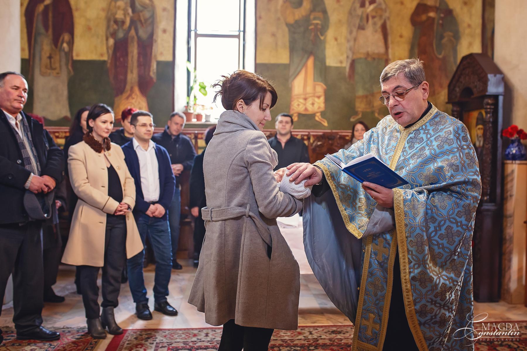 Fotograf la botezul mariei biserica in brate la nasa preotul cu mana pe capul ei