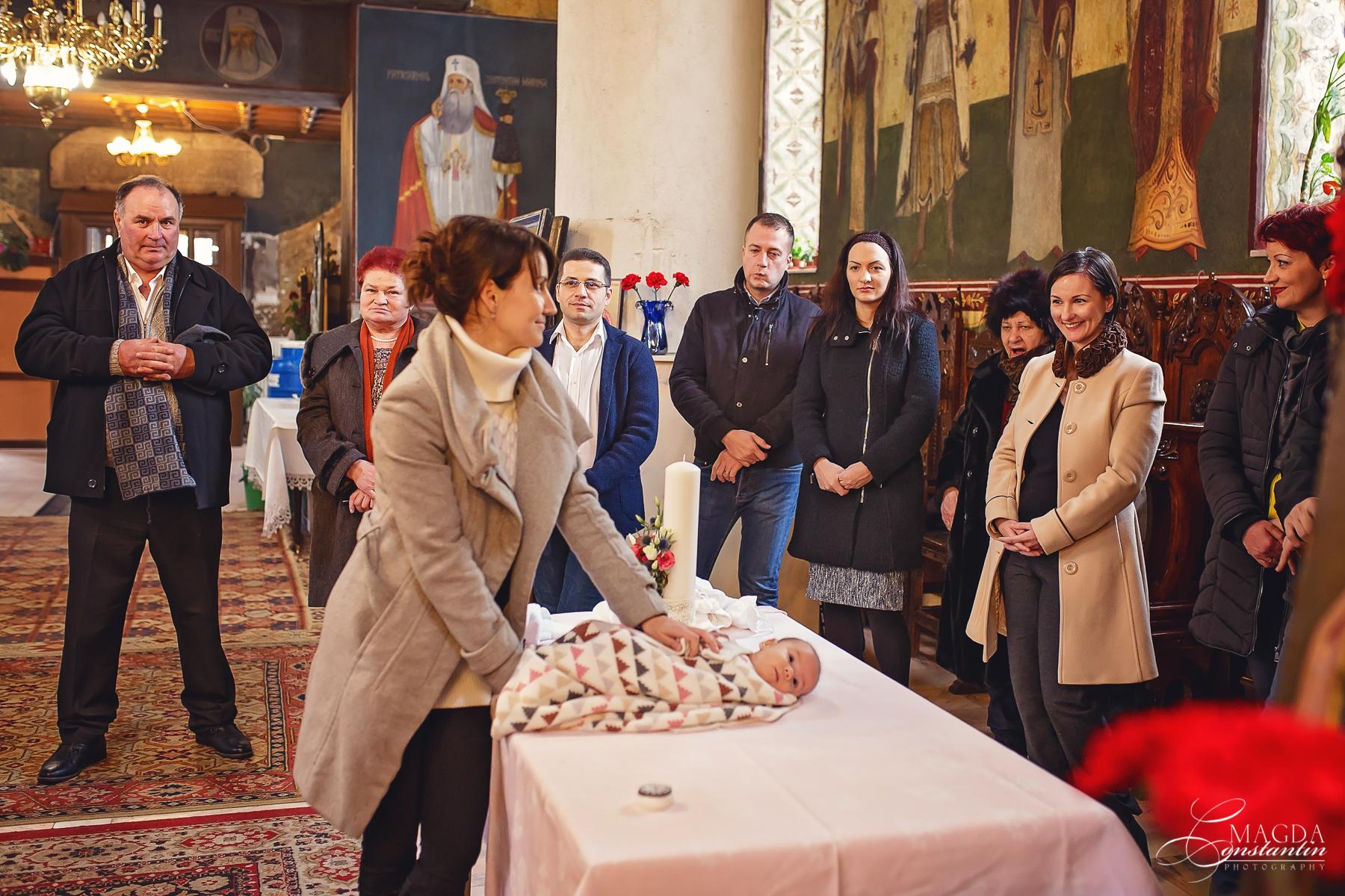 Fotograf la botezul mariei biserica pe masa cativa invitati focus pe mama