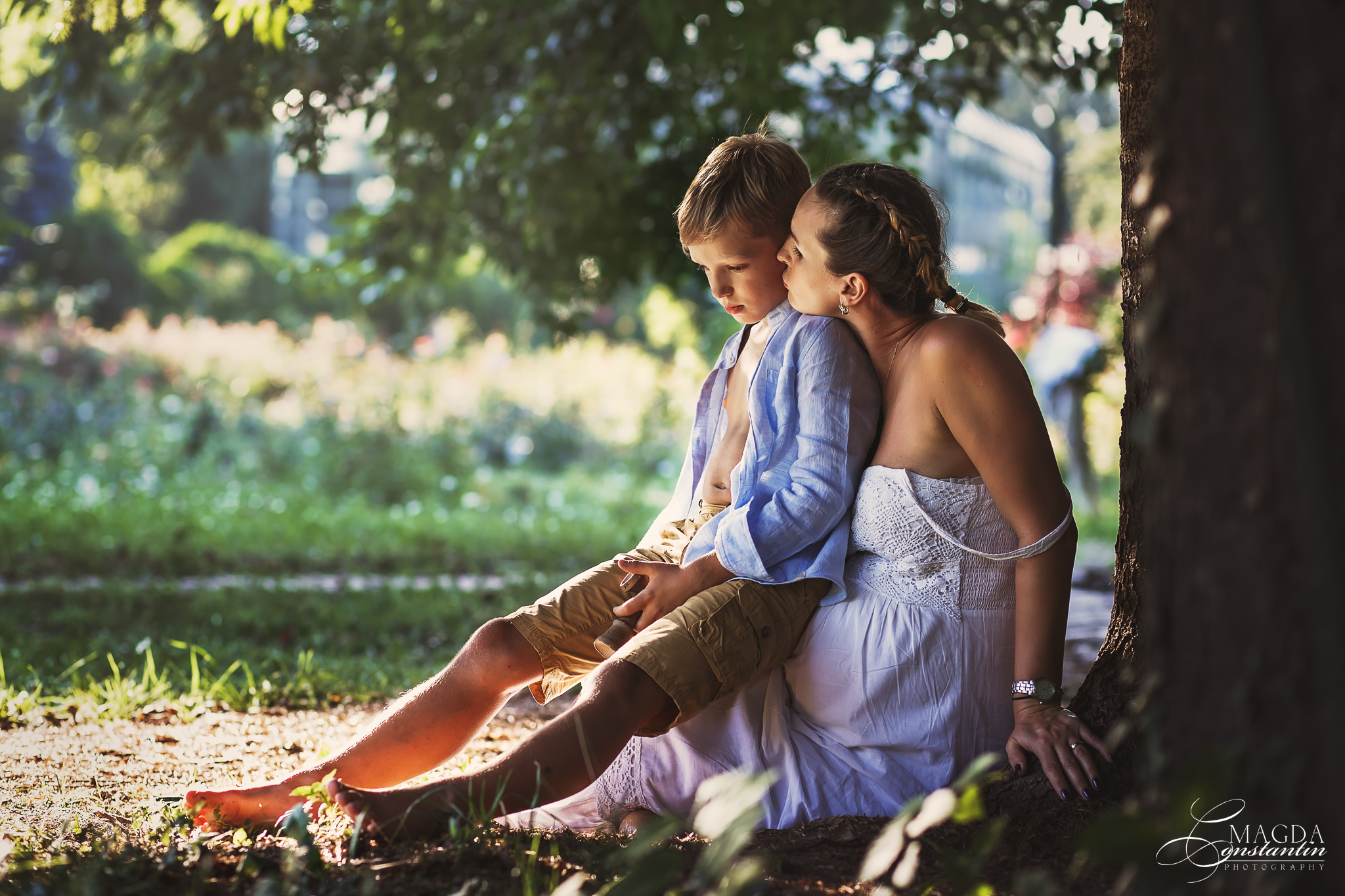 Sedinta foto de maternitate in natura cu stefania si baiatul ei cel mare asezati sprijiniti de copac in gradina botanica