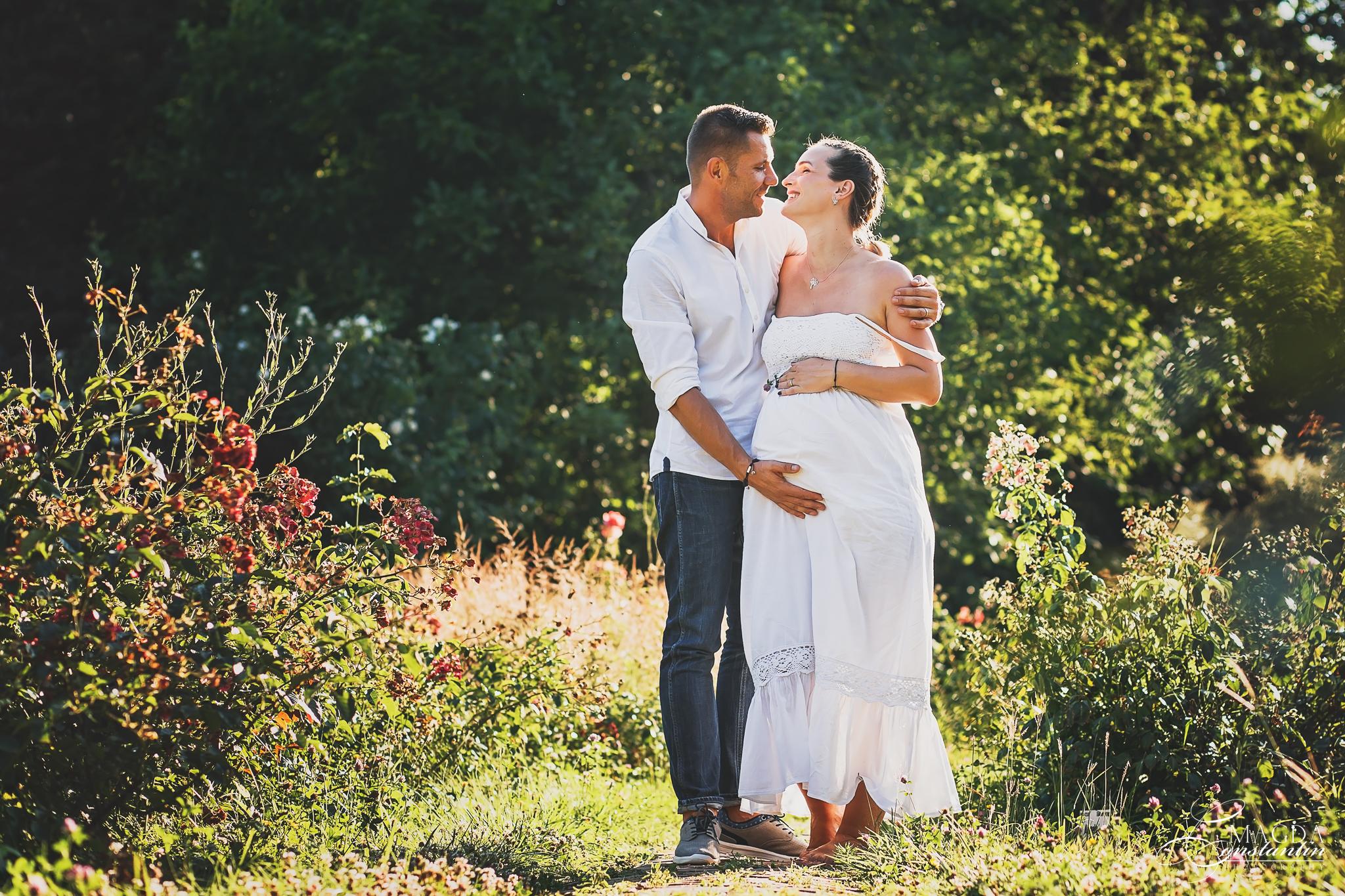 Sedinta foto de maternitate in natura cu stefania si sotul tinandu-se in brate si razand in contra luminii cu trandafiri rosii in gradina botanica
