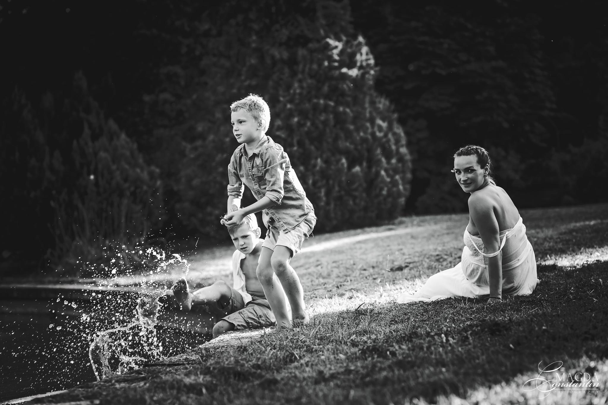 Sedinta foto de maternitate in natura cu stefania si cei doi baieti jucandu-se pe malul lacului in alb-negru in gradina botanica