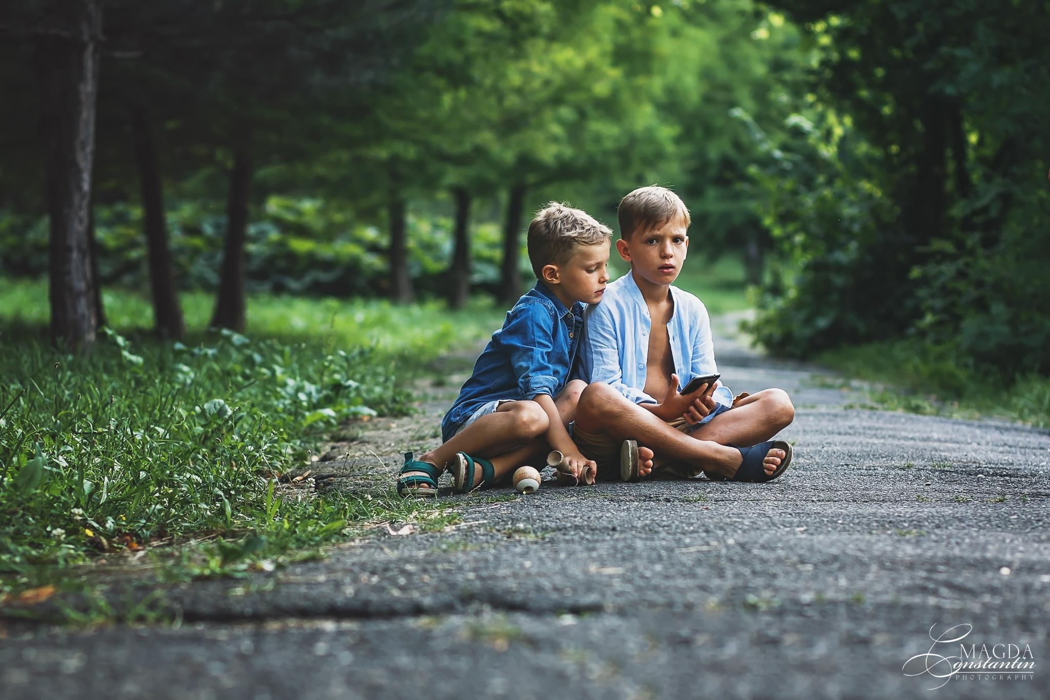 Sedinta foto de maternitate in natura cu stefania cei doi baieti asezati pe o alee in gradina botanica