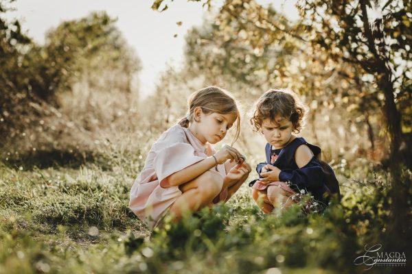 Fotografie de familie in natura - doua surori stand pe iarba, in lumina calda, toamna