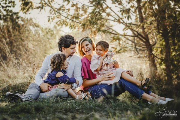 Fotografie de familie in natura - familie stand pe iarba, in lumina calda, toamna