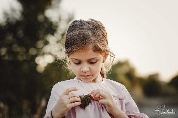Fotografie de familie in natura - fetita jucandu-se cu o inimioara din muschi de copac, in lumina calda, toamna