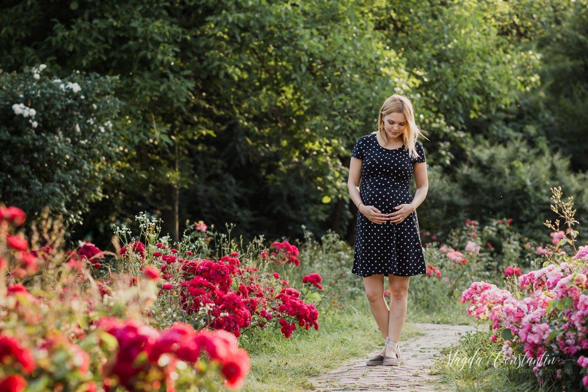 Sedinta foto de gravide in natura, lifestyle si familie, in Bucuresti, mama in picioare cu mainile pe burtica, trandafiri rosii si roz, cu lavinia - 4