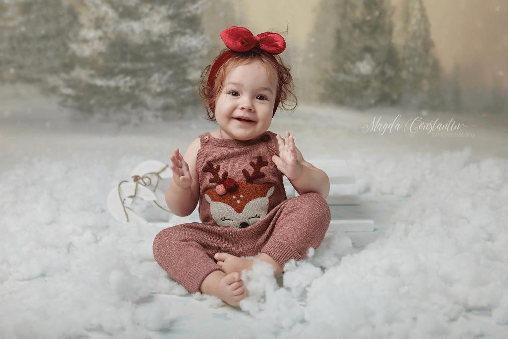 sedinta foto de craciun in bucuresti, fetita in zapada cu funda rosie